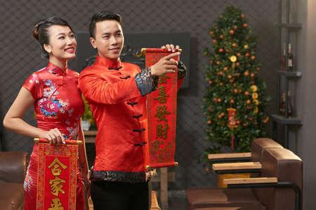 Jong Vietnamees paar die de traditionele kostuums dragen die rollen met Nieuwjaarhoofden in handen houden terwijl omhoog verpakt in woonkamerdecoratie