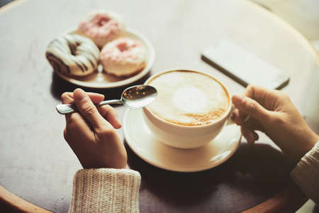 Unrecognizable young woman wearing knitted cardigan enjoying fragrant cappuccino and delicious doughnuts while sitting at cozy small cafe Stock Photo