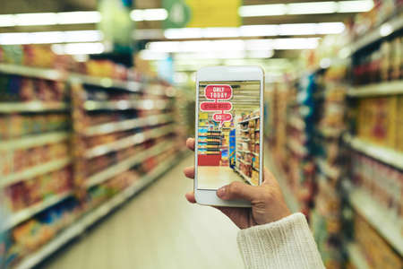 Close-up shot of young woman doing shopping at hypermarket with help of augmented reality app, blurred background Stock Photo