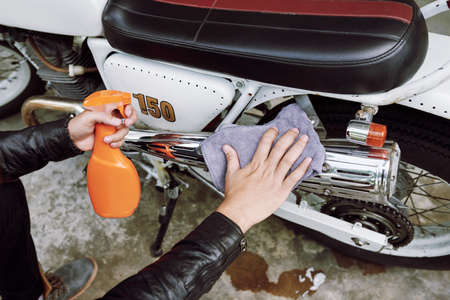 Close-up shot of unrecognizable man sitting on haunches and wiping dirt from his motorcycle with help of rag and cleaning spray