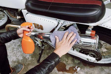 Close-up shot van onherkenbare man zit op hurken en vuile vuil van zijn motorfiets met behulp van rag en schoonmaak spray
