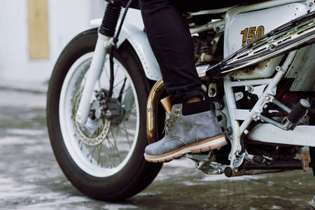 throttle: Close-up shot of male foot pressing gas pedal on vintage motorcycle, close-up shot