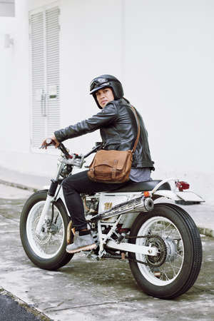 Full length portrait of confident brutal man wearing helmet and leather jacket posing for photography while sitting on vintage motorcycle ready for searching adventures