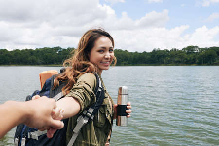 Vietnamese female hiker with thermos holding hand of her boyfriend when walking by lake