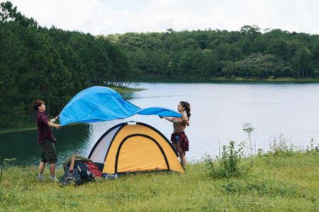 彼らを組み立てるテントにカバーを置く旅行者のカップル