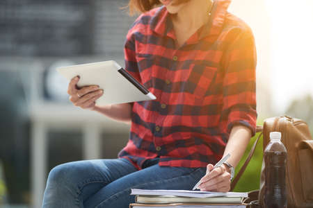 application university: Cropped image of student reading information on tablet computer and taking notes