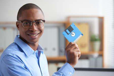 Lächelnder Büroangestellter, der Diskette mit Informationen zeigt