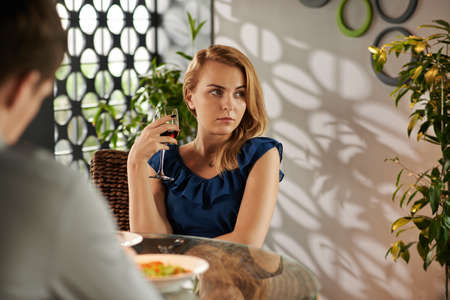 blind date: Unhappy pretty young woman drinking wine during blind date in restaurant Stock Photo