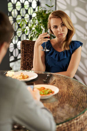 blind date: Unhappy woman thinking and drinking wine when her boyfriend texting to friends during date