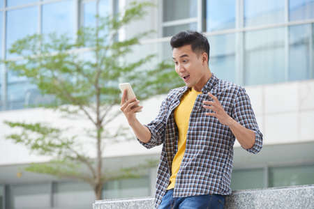 Shocked Asian young man looking at screen on his smartphone Stock Photo