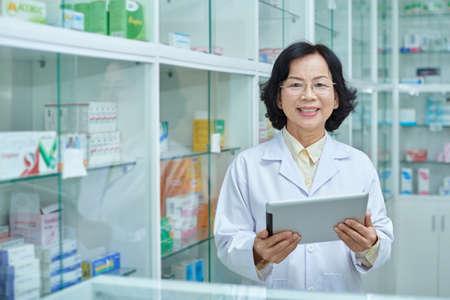 Portrait on mature Vietnamese drugstore provisor with digital tablet