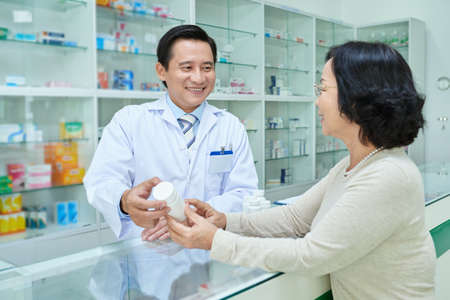Professional Vietnamese pharmacist telling benefits of new medicine to the customer Фото со стока