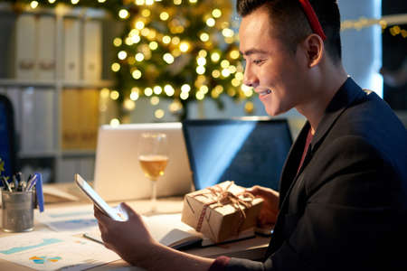 Young businessman congratulating friends with New Year via text messages Stock Photo