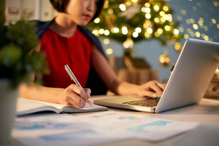 Business lady writing plans for the nest year on Christmas night Archivio Fotografico