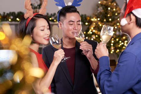 Vietnamese business people enjoying champagne at Christmas party Stock Photo