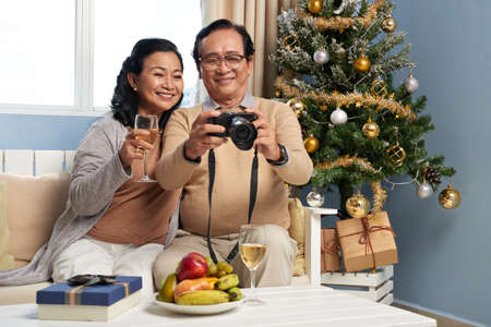 Senior husband and wife drinking champagne and watching photos on camera on Christmas eve