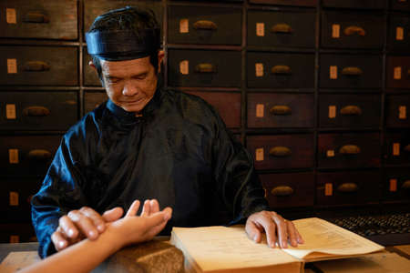 Chinese medicine practitioner checking pulse of female patient