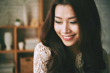 Face of pretty Asian young woman smiling when dreaming