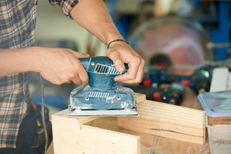 Close-up image of carpenter polishing wooden plank with sanding machine