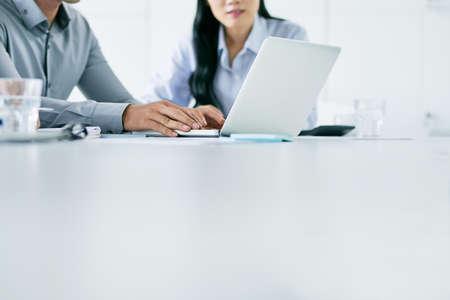 大きな白いテーブルで一緒に働くビジネスマンのトリミングされたイメージ