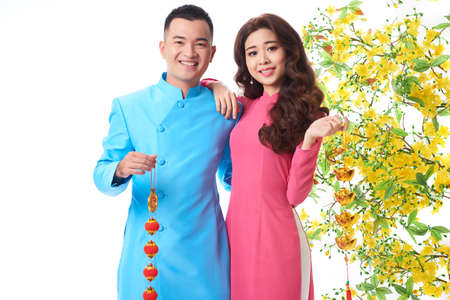 Cheerful couple with Tet decorations