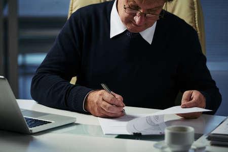 Businessman checking financial document on his table Imagens