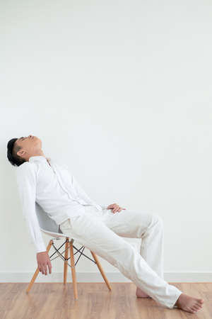 Tired young Asian man sleeping on chair