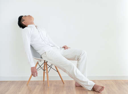 Young Asian man in simple white clothes sleeping on chair Foto de archivo
