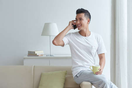 Handsome young Asian man with a cup of tea sitting on hi sofa and calling on the phone