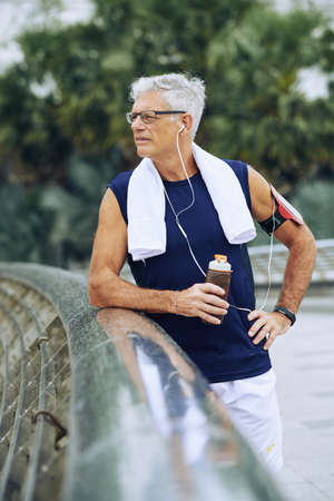 Elderly man drinking water after jogging in the morning