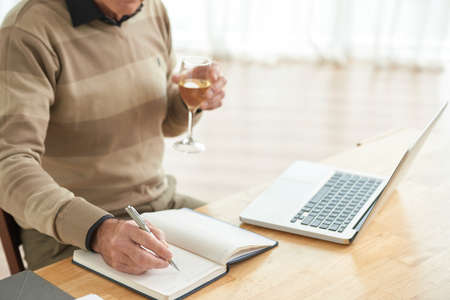 Man with glass of wine writing plans in his notepad