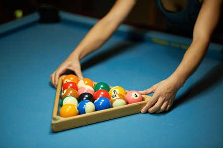 Player using triangle to rack up billiard balls