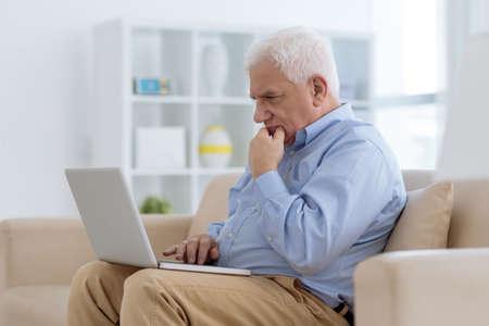 Aged man working on laptop