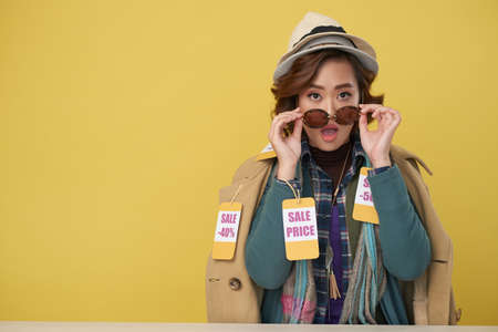 Portrait of surprised Asian woman wearing sunglasses and layers of clothes with sale labels, copy space to the left
