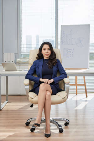 Full length portrait of highly professional young manager posing for photography while sitting on chair with legs crossed, interior of spacious office on background Stock Photo