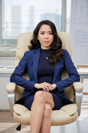 Confident Asian entrepreneur in formalwear sitting at office chair with legs crossed and looking at camera, full length portrait shot