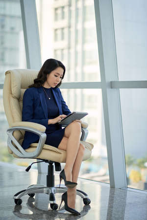 Confident young entrepreneur sitting at office desk with crossed legs and working on promising project with help of digital tablet, interior of modern office on background