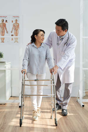 Middle-aged physiotherapist wearing white coat helping his senior patient to use front-wheeled walker while standing at modern office Standard-Bild