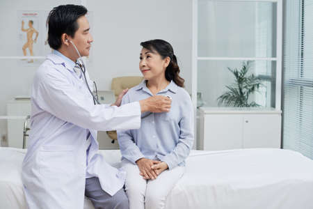 Profile view of confident middle-aged therapist wearing white coat using stethoscope while examining senior patient, interior of modern ward on background 写真素材