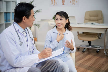 Pretty aged woman sitting on cozy sofa and describing medical symptoms to confident physician while having consultation at modern office