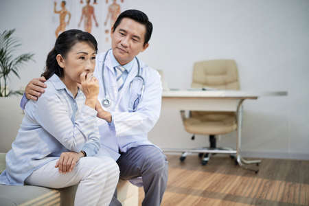 Handsome Asian physician sitting on sofa of modern office and calming down sad senior woman after announcement of diagnosis Stock Photo