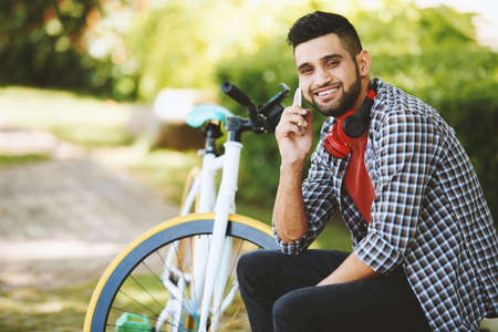 Cheerful Indian man looking at camera with toothy smile while talking to friend on smartphone and sitting on park bench, modern bicycle on background