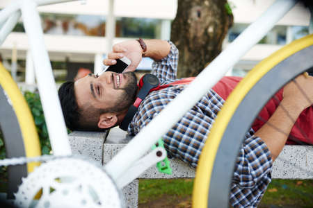 Handsome Indian cyclist wearing red T-shirt and checked shirt lying on bench of green public park and talking to friend on smartphone, portrait shot Stock Photo