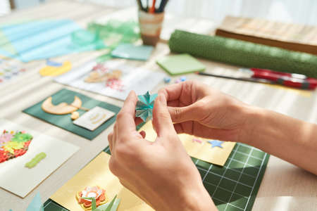 Unrecognizable young woman making decorative elements for her handmade greeting card while sitting at wooden table