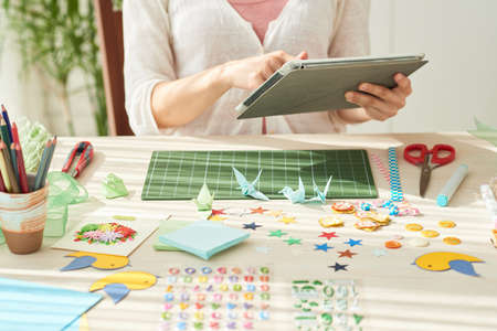 Young woman sitting at wooden table and using digital tablet while taking break from making origami cranes, decorative items and tools on foreground