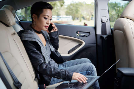 Young woman in leather jacket sitting in car, making phone calls and working on laptop Stock Photo