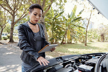 Woman following instructions on digital tablet when checking her car Stock Photo