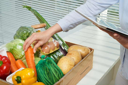Hands of man checking fresh ogranic vegetables in the parcel her ordered