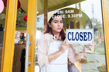 Unhappy young female confectionery owner closing her store