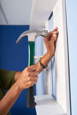 Hands of woman hammering nail into wall